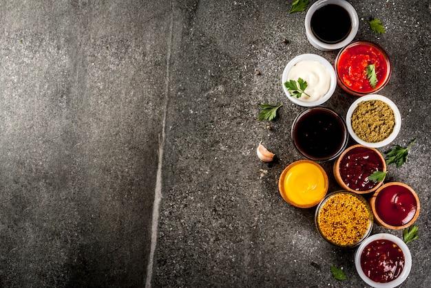 Set of different sauces  ketchup, mayonnaise, barbecue, soy, teriyaki, mustard, grain hills, pesto, adzhika, chutney, tkemali, pomegranate sauce on black stone .  top view