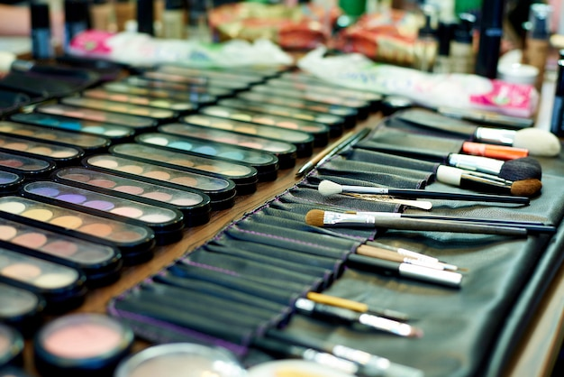A set of different shadows and makeup brushes close-up.