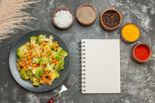 Set di diverse spezie in ciotole marroni e insalata di verdure con broccoli freschi e taccuino