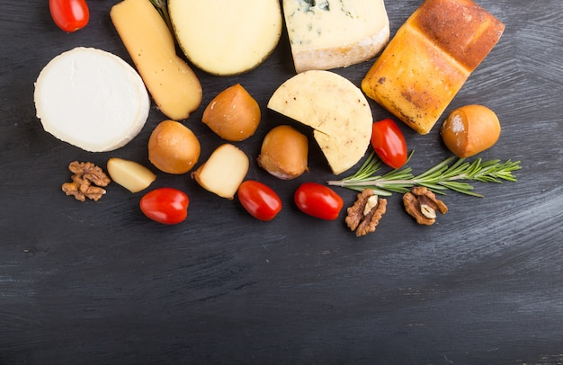 Set of different types of cheese with rosemary and tomatoes on a black wooden background . top view, copy space.