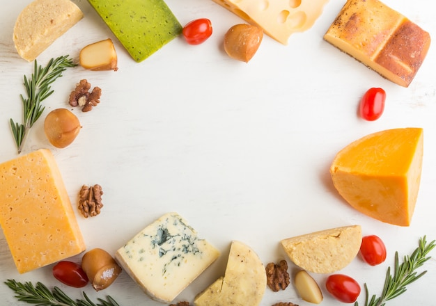 Set of different types of cheese with rosemary and tomatoes in the shape of a frame on a white wooden background . top view, copy space.