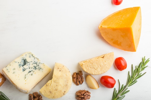 Set of different types of cheese with rosemary and tomatoes on a white wooden background . top view, copy space.