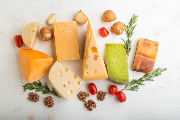 Set of different types of cheese with rosemary and tomatoes on a white wooden background . top view.