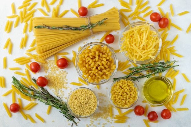 A set of different types of dry pasta and ingredients for cooking are laid out on a light surface. horizontal orientation, selective focus, top view.