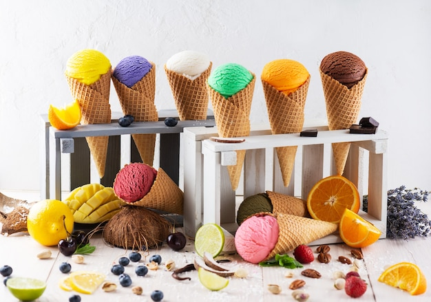 A set of different types of ice cream in waffle cones in a wooden boxes