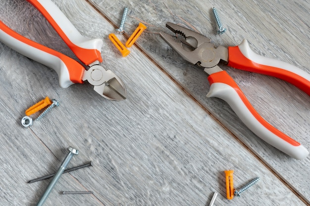 Set of different types of pliers, side knives and fasteners on a gray laminate