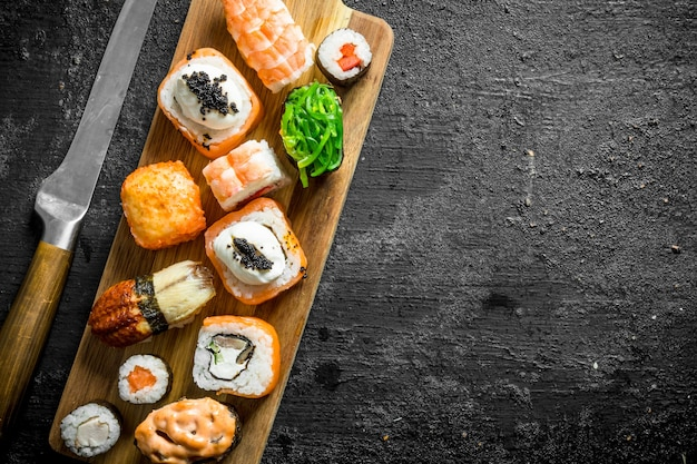 Set of different types of sushi and rolls on wooden cutting board. on black rustic surface