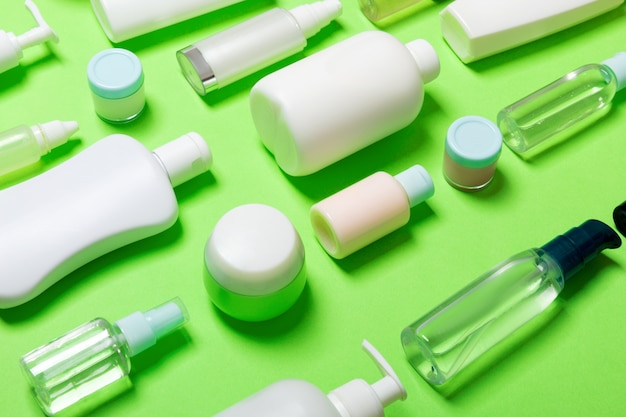 Set of diffrent sized bottles and jars for cosmetic products on green backgound