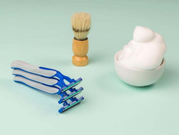 A set of disposable razors, foam and shaving brush on blue