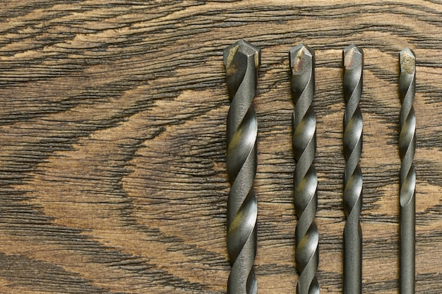 Set of drill bits on a wooden table, close up