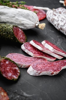 Set of dry cured salami, spanish sausages, slices and cuts on black background
