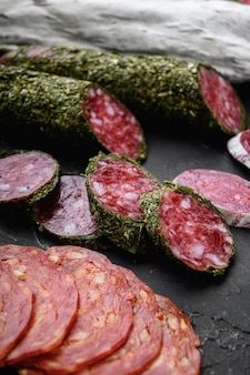 Set of dry cured salami, spanish sausages, slices and cuts on black textured surface