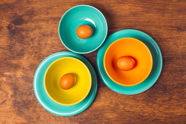 Set di uova di pasqua su piatti luminosi e ciotole
