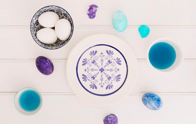 Set di uova di pasqua tra tazze di liquido colorante e piastra