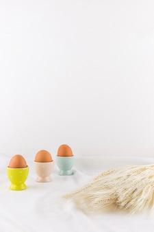 Set di uova di pasqua in tazze vicino mazzo di grano sul tessile leggero