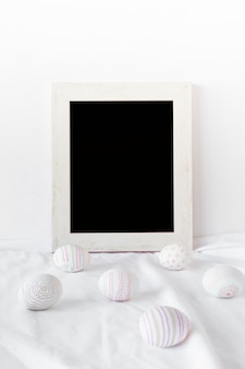 Set of easter eggs near photo frame on textile