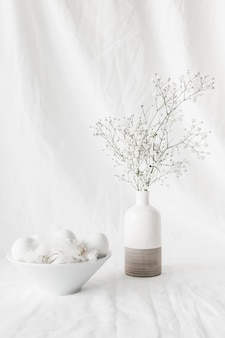 Set of easter eggs and quills in bowl near plant branches in vase