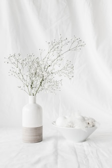 Set of easter eggs and quills in bowl near plant twigs in vase