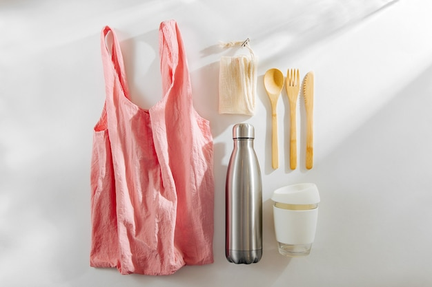 Set of eco friendly bamboo cutlery, pink eco bag  reusable coffee mug  and  water bottle.