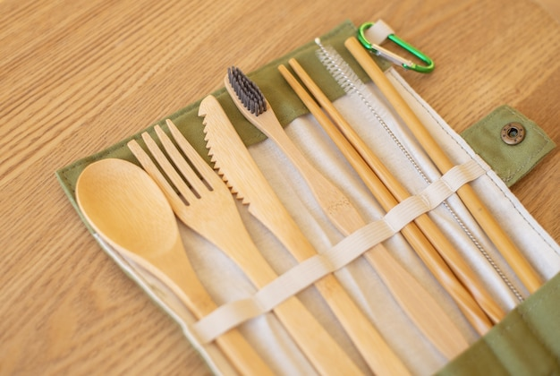 Set of eco friendly bamboo cutlery on wood table. sustainable lifestyle. plastic free concept. close-up, top view.