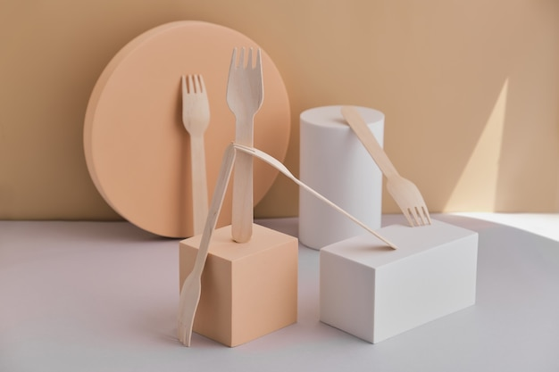 Set of eco-friendly tableware, wooden forks placed on trendy podiums and geometric pedestals