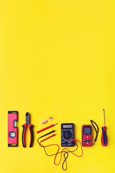 Set of electrician's tools on yellow background. flat lay composition with electrician's tool