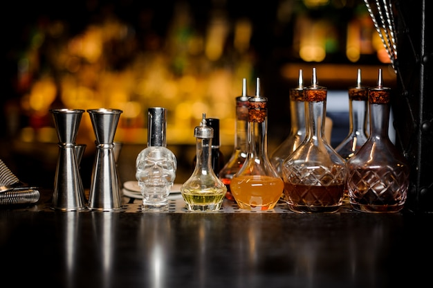 Set of elegant barman tools including jiggers and little bottles with liquor
