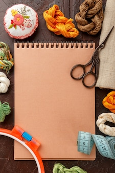 Set for embroidery, embroidery hoop, linen fabric, thread, scissors, embroidered needle bed and notepad. top view