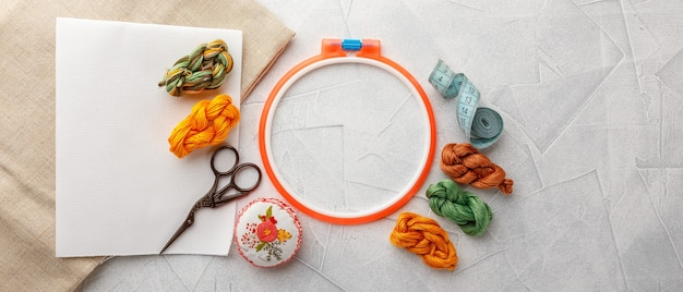 Set for embroidery, embroidery hoop, linen fabric, thread, scissors, embroidered needle bed. top view