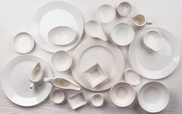 Set of empty dishware on white surface