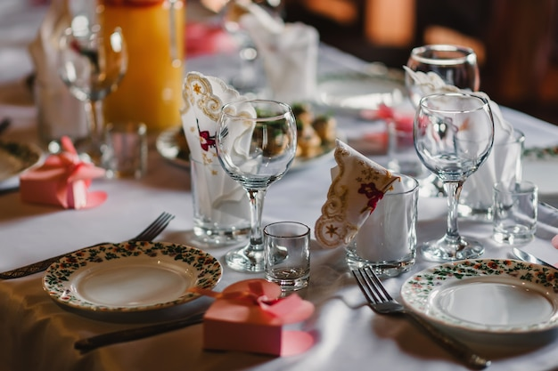 Set of empty glasses and plates with cutlery on a white tablecloth on the table in the restaurant
