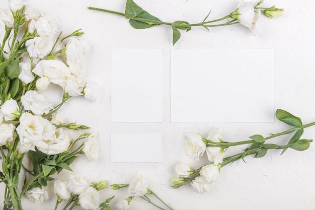 흰색 eustoma lisianthus 꽃, 결혼식 초대 디자인 요소, 감사 또는 인사말 카드가 있는 3개의 카드 모형이 비어 있습니다. 봄 배경