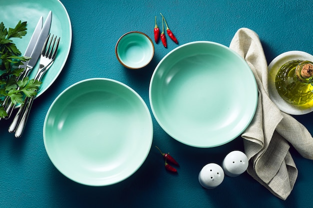 Set of empty plates on a blue table.