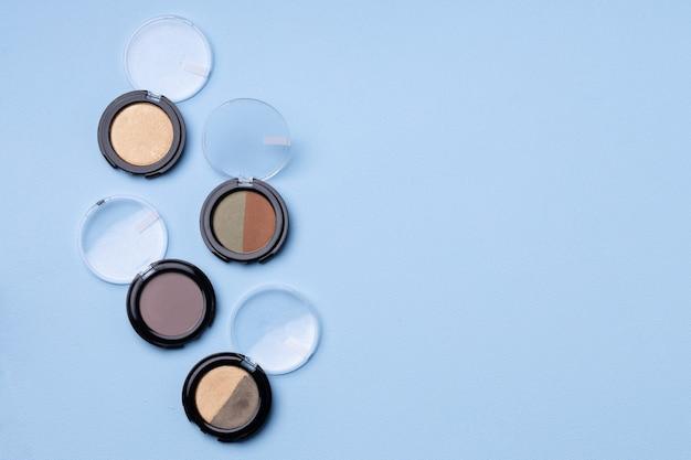 Set of eyeshadows on blue close up photo