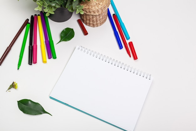 Set of felt tip markers in different colors and a blank sketchbook