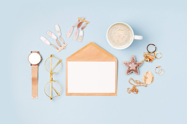 Set of female accessory and envelope with mockup card on blue background. flat lay