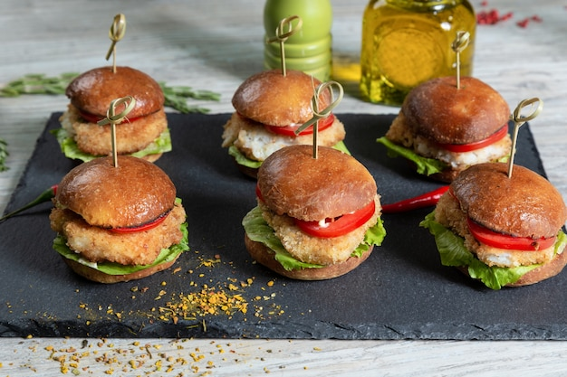 Set of fish burgers on black board on wooden table
