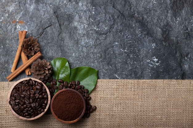 Set flat lay coffee beans in wood cup on green leaf , pine on burlap on black stone