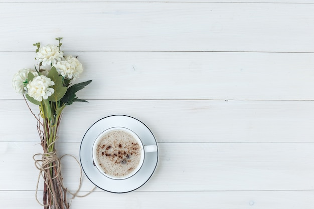 Set of flowers and coffee in a cup on a wooden background. top view.