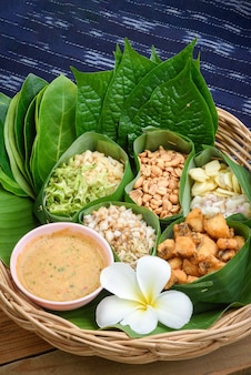 Set of food wrapped in leaves called miang lay on banana leaf