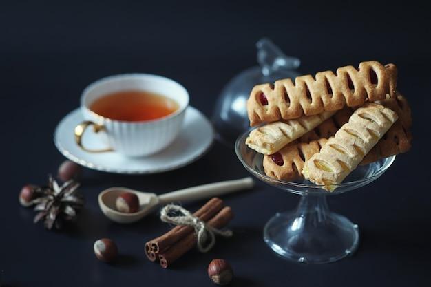 朝食用に設定します。黒の背景にお茶のナッツとお菓子やペストリー。コーヒーカップとパテ。