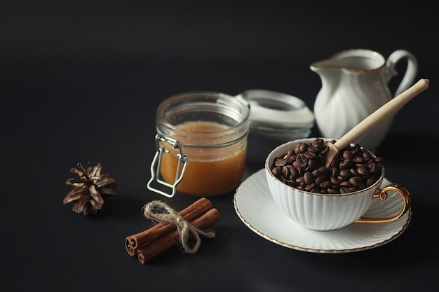 아침 식사를 위해 설정합니다. 검은 배경에 차를 위한 견과류와 과자와 패스트리. 커피잔과 패티.