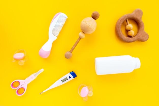 노란색 배경, 위쪽 전망, 평평한 평지에 어린이 위생을 위해 설정합니다. 신생아를 돌보는 것을 의미합니다. 트렌디한 아기 개념, 밝은 배경.