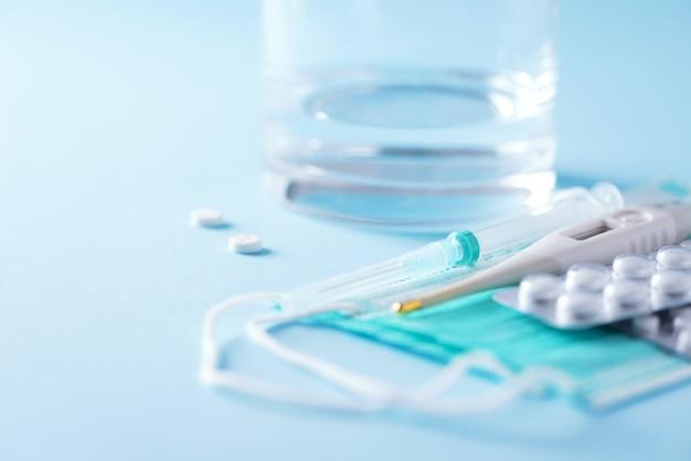 Набор для лечения гриппа - таблетки, капсулы, термометр, защитная хирургическая маска, шприц. копировать пространство баннер. вирусная атака. куча лекарств, лечение простуды. коронавирус ковид-19
