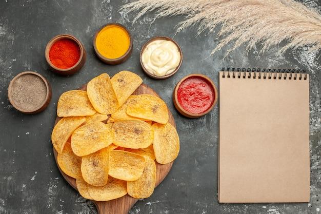 ノートの横にさまざまなスパイスマヨネーズとケチャップを含むポテトチップス用に設定