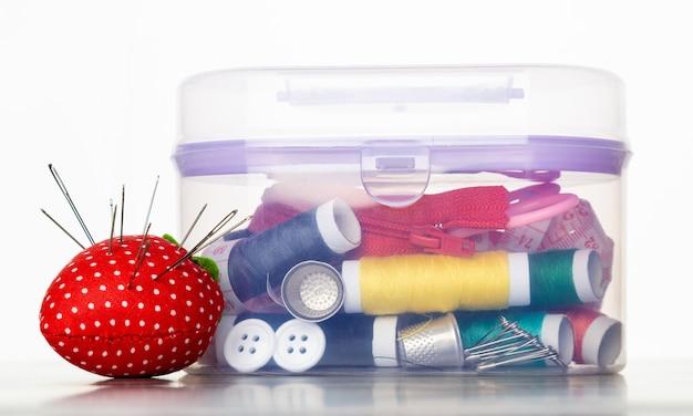 Набор для шитья и ремонта в пластиковой коробке на белом фоне
