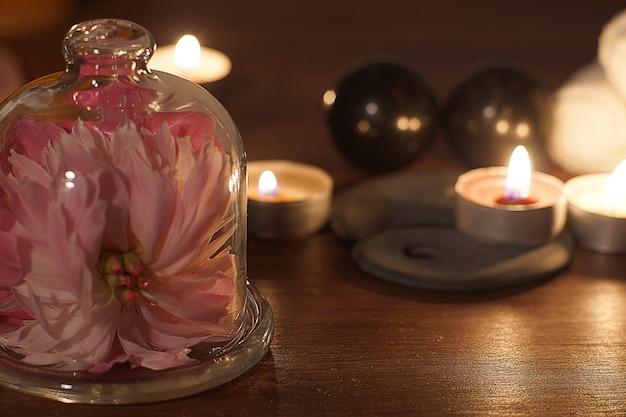 フードの下にスキンケアタオルとピンクの花を使ったspa手順用に設定
