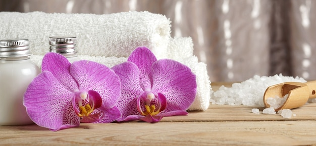 肌用ローション、蘭の花、バスソルト、白いタオルでスパトリートメントをお楽しみいただけます