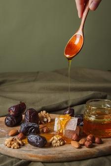 Набор для чаепития. рука, держащая ложку с капающим медом. различные сладости, орехи и мед для чая на деревянной разделочной доске. полезные сладости, вкусный десерт, натуральные сладости.