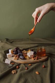 お茶を飲むためのセット。はちみつが滴るスプーンを持っている手。木製のまな板にお茶用のさまざまなお菓子、ナッツ、蜂蜜。ヘルシースイーツ、美味しいデザート、ナチュラルスイーツ。